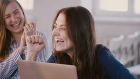 Ung lycklig tillfällig europeisk kvinnlig kontorschef som skrattar och att le, medan diskutera arbete på kläckning av ideerper arkivfilmer