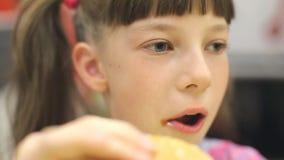 Ung lycklig tonåring som äter den smakliga hamburgaren i snabbmatrestaurang Den tonåriga flickan som äter fransman, steker för ma arkivfilmer