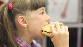Ung lycklig tonåring som äter den smakliga hamburgaren i snabbmatrestaurang Den tonåriga flickan som äter fransman, steker för ma lager videofilmer