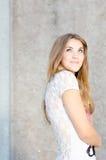 Ung lycklig tonårs- flicka som ser stå upp på grå väggbakgrundscopyspace Royaltyfri Bild