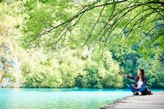 Ung lycklig turist- kvinna med ryggsäcksammanträde på träbron som tycker om härlig sikt fotografering för bildbyråer