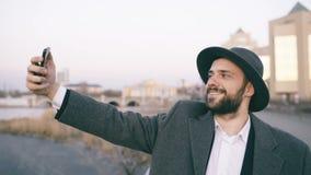 Ung lycklig turist- man i ahat och lag som ler, medan ta selfiebilden med mobiltelefonen på stadsflodstranden arkivfilmer