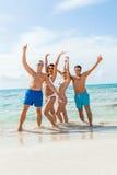 Ung lycklig vänhavingyckel på stranden royaltyfri foto