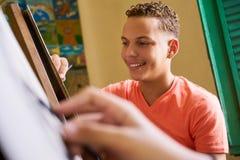 Ung målning konstnärDrawing In College för ung man på skolan Royaltyfria Bilder
