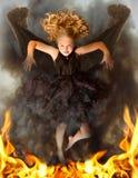 Ung mörk ängel som stiger från flammorna Arkivfoton