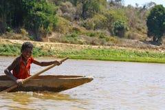 Ung madagassisk afrikansk pojke som ror den traditionella kanoten Arkivbilder