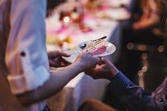 Ung mager flicka som lite räcker ett stycke av kakan på plattan till a royaltyfri bild