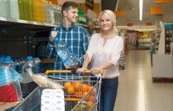 Ung make och fru som köper vattnet på lagret royaltyfria bilder