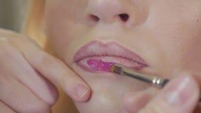 Ung makeupkonstnär som applicerar läppstift på kanter för modell` s lager videofilmer
