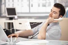 Ung male sitting på skrivbordet som talar på telefonen fotografering för bildbyråer