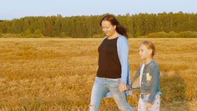 Ung mamma och dotter som går på vetefält medan höstplockning lager videofilmer