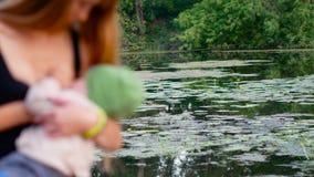 Ung mamma som brestfeeding hennes för son defocus utomhus lager videofilmer
