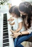 Ung mamma som spelar pianot med hennes lilla dotter arkivbild