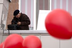 Ung man över den isolerade blåa väggen som rymmer en kamera - Ryssland Berezniki kan 9, 2018 fotografering för bildbyråer