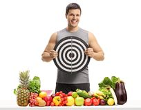 Ung man bak en tabell med frukt och grönsaker som rymmer en tjära Royaltyfri Bild