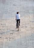 Ung man för bakre sikt som cyklar på gatan Arkivbild