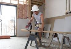 Ung man för byggmästarebranschdeltagare i utbildning på hans 20-tal som bär den skyddande hjälmen som lär att arbeta på den indus Arkivfoto