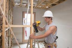 Ung man för byggmästarebranschdeltagare i utbildning på hans 20-tal som bär den skyddande hjälmen som lär att arbeta med drillbor Arkivbilder