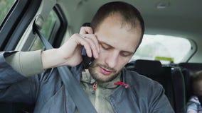 Ung man för Closeup som talar på mobiltelefonen, medan rida i backseat av bilen stock video