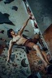 Ung man för fri klättrare som inomhus klättrar den konstgjorda stenblocket royaltyfri foto