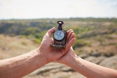 Ung man för handelsresande som söker riktning med en kompass i sommarberg Punkt av siktsskottet royaltyfria bilder