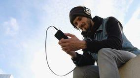 Ung man för lågt skott som sitter i tillbaka ljus och lyssnar till musik, himmelbakgrund stock video
