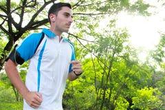 Ung man för sportig passform som joggar medan lyssnande musik Royaltyfri Bild