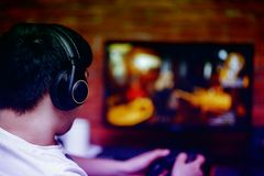 Ung man för teknologi-, dobbel-, underhållning-, lek- och folkbegrepp i hörlurar med mikrofon med kontrollantgamepad som spelar d arkivfoton