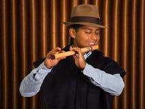 Ung man från Otavalo, Ecuador som spelar quenaflöjten Arkivfoto