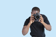 Ung man för afrikansk amerikan som tar fotoet till och med digital kamera över blå bakgrund Royaltyfri Foto