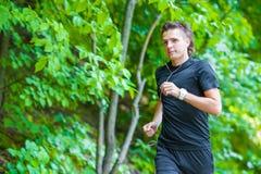 Ung man för sportig passform som joggar medan lyssnande musik Royaltyfria Foton