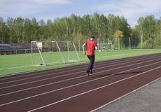 Ung man, i att göra övning På stadion fotografering för bildbyråer