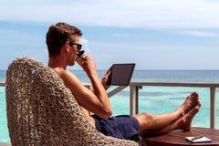 Ung man i baddräkt som dricker kaffe och arbetar på en minnestavla i en tropisk destination royaltyfria foton