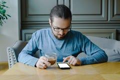 Ung man i caffe med smartphonen medan affärsavbrott royaltyfri bild