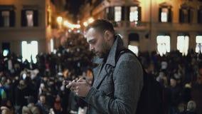 Ung man i centrum i aftonen Manligt bruk smartphoneanseendet på fyrkanten i folkmassa i stadsmitt royaltyfri fotografi