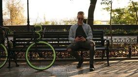 Ung man i den blåa skjortan som sittting på bänken och rymmer hans mobiltelefon i händer som smsar Att ta för ryttare vilar efter arkivfilmer