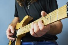 Ung man i den svarta skjortan som spelar den elektriska gitarren royaltyfri bild