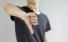 Ung man i den svarta t-skjortan som visar ett tecken av motvilja, isolerad nolla royaltyfri bild