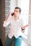 Ung man i den vita skjortan som talar över telefonen med frågande uttryck Arkivfoton