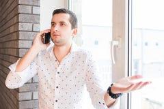 Ung man i den vita skjortan som talar över telefonen med frågande uttryck Arkivfoto