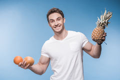 Ung man i den vita t-skjortan som rymmer nya frukter och ler på kameran Royaltyfri Foto
