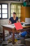 Ung man i det mycket smutsiga kontoret som ser förbryllat Royaltyfri Foto
