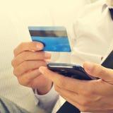 Ung man i dräkt genom att använda hans kreditkort direktanslutet royaltyfri fotografi