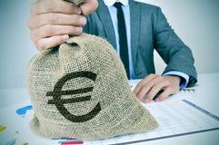 Ung man i dräkt med en säckvävpengarpåse med eurotecknet Arkivfoto