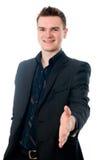 Ung man i dräkten som erbjuder att skaka handen Fotografering för Bildbyråer
