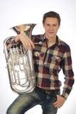 Ung man i dräkten som rymmer en trumpethorn Arkivbild
