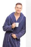 Ung man i en badrock som rymmer en kopp kaffe Arkivfoton
