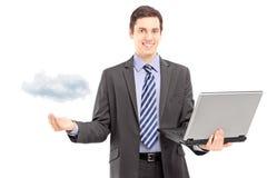 Ung man i en dräkt som rymmer en bärbar dator som symboliserar molnberäkning Royaltyfri Fotografi