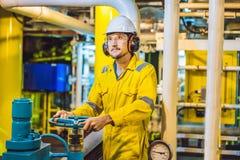 Ung man i en gul arbetslikformig, exponeringsglas och hj?lm i bruksmilj?, oljaplattform eller v?xt f?r sm?lt gas arkivbilder