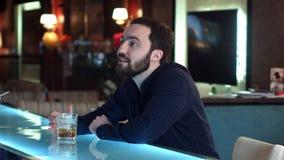 Ung man i en stång som har en konversation med bartendern och att dricka Fotografering för Bildbyråer